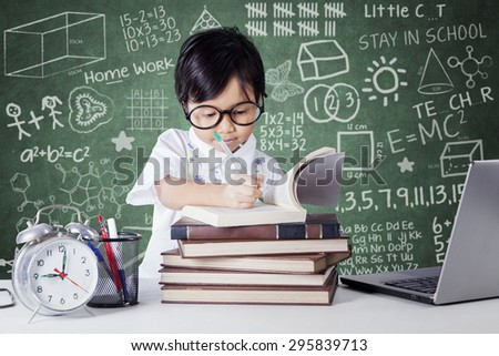 Portrait of cute little girl writing on the book in the classroom with alarm clock and laptop computer on the table - stock photo