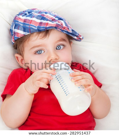 Portrait of cute little hungry baby boy drinking milk, lying on the bed and eating, baby food formula, healthy nutrition for kids - stock photo