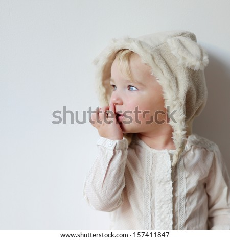 Portrait of cute little one year old baby girl in funny hat with ears - stock photo