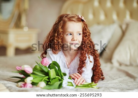 Portrait of cute little redhead girl with tulips in her room - stock photo