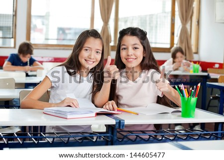 Portrait of cute little schoolgirls gesturing thumbs up while sitting together at desk in classroom - stock photo