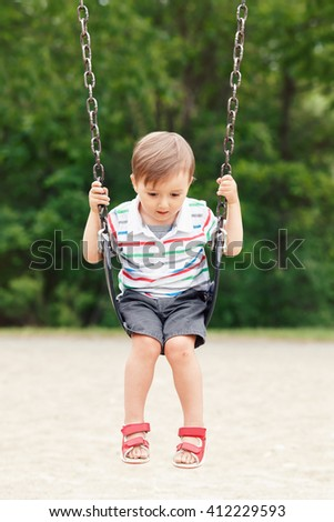 Portrait of cute little small boy toddler looking away, wearing tshirt and jeans shorts on swing on backyard playground outside on summer day, happy childhood lifestyle - stock photo