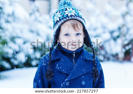 Portrait of cute little toddler boy with blue eyes in winter clothes - coat and hat - with falling snow. Kid enjoying and catching snowflakes, outdoors on cold day. - stock photo
