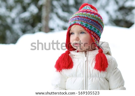 Portrait of cute little toddler girl in beautiful warm outfit playing outdoors in the snow - stock photo