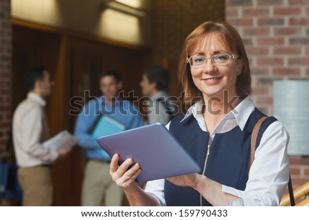 Portrait of cute mature student holding her tablet smiling at camera - stock photo