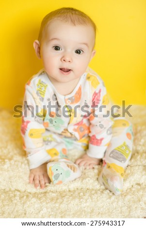 portrait of cute newborn baby sitting on a yellow wall background - stock photo