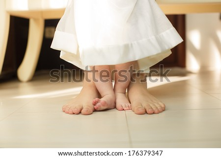 portrait of Cute newborn foot with family members standing on the floor - stock photo