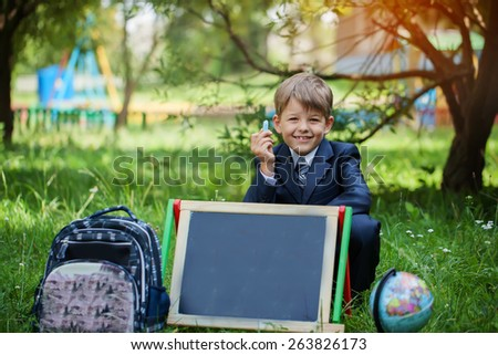 Portrait of cute school boy with backpack and backboard  in the park, sunny day - stock photo