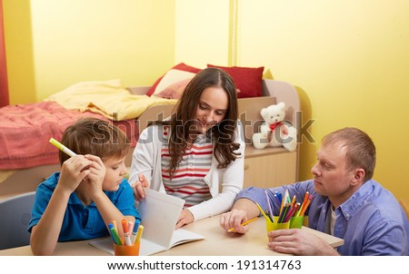 Portrait of cute schoolboy and his parents making schoolwork at home - stock photo