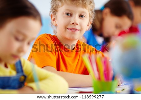 Portrait of cute schoolboy at workplace looking at camera among his classmates - stock photo