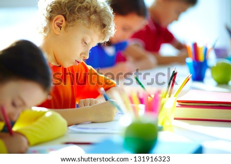 Portrait of cute schoolboy drawing at workplace among his classmates - stock photo
