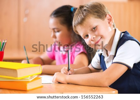 Portrait of cute schoolboy during lesson in classroom at school - stock photo