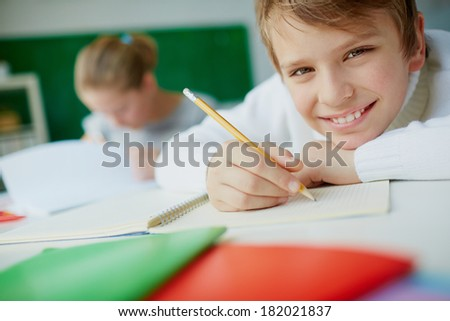 Portrait of cute schoolboy looking at camera while drawing - stock photo