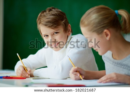 Portrait of cute schoolboy looking at camera while drawing at lesson with his classmate near by - stock photo