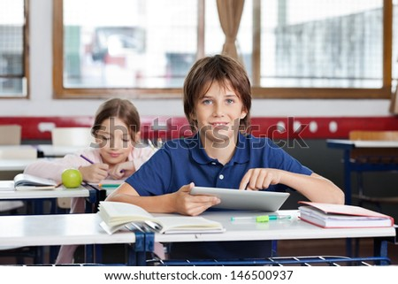 Portrait of cute schoolboy using digital tablet with schoolgirl in background at classroom - stock photo