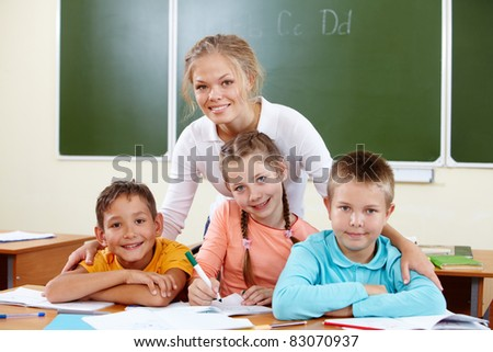 Portrait of cute schoolchildren and teacher in classroom - stock photo