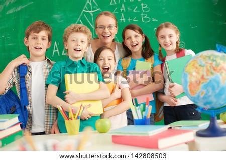 Portrait of cute schoolchildren and their teacher on background of blackboard - stock photo