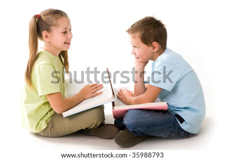 Portrait of cute schoolchildren holding open books and communicating - stock photo