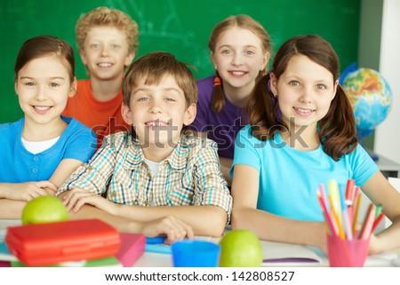 Portrait of cute schoolchildren looking at camera in classroom - stock photo