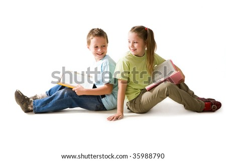 Portrait of cute schoolchildren sitting on the floor with open books - stock photo