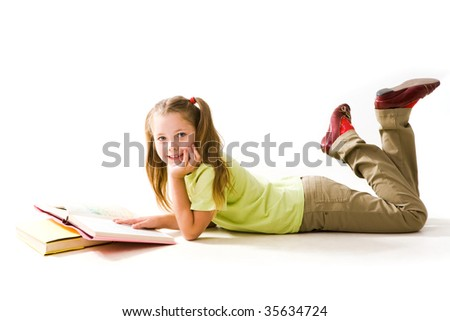 Portrait of cute schoolgirl keeping her hand on open book and looking at camera - stock photo