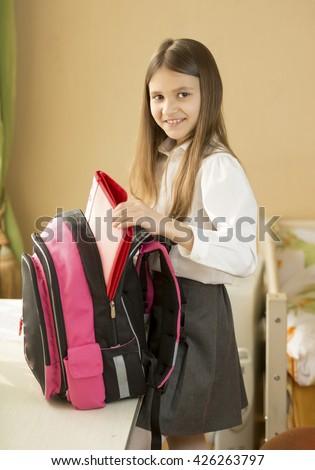 Portrait of cute schoolgirl packing her bag at bedroom - stock photo