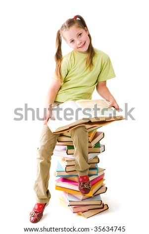 Portrait of cute schoolgirl sitting on top of heap with open book and looking at camera - stock photo