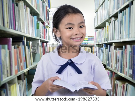 Portrait of cute schoolgirl smiling while reading a book in library - stock photo