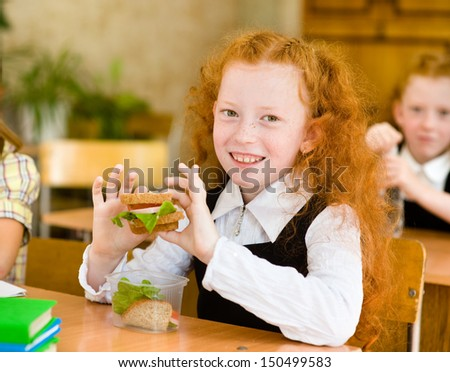 Portrait of cute schoolgirl with sandwich looking at camera in classroom - stock photo