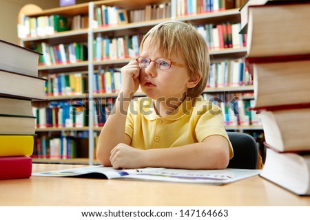 Portrait of cute schoolkid sitting in the library - stock photo