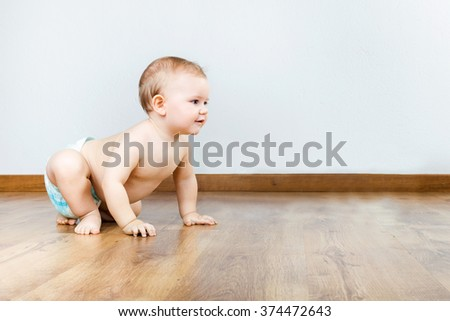 Portrait of cute smiling baby sitting at home. - stock photo
