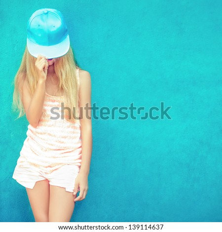 Portrait of cute teen girl in blue wall - stock photo
