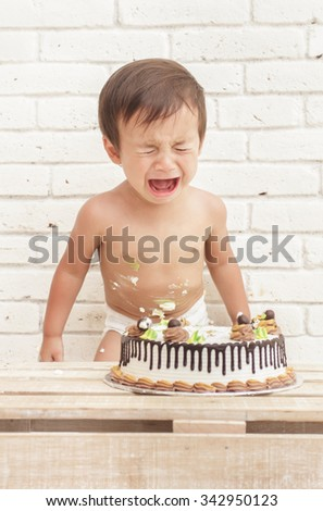 portrait of cute toddler crying while playing smash cake - stock photo