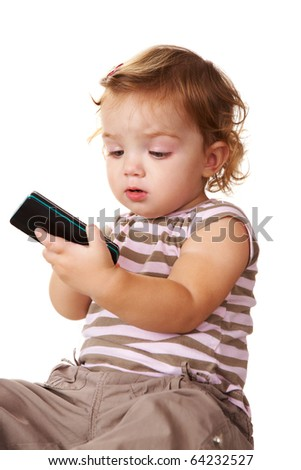 Portrait of cute toddler looking at cellular phone in her hands - stock photo