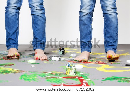 Portrait of cute twin girls with finger paintings having fun - stock photo