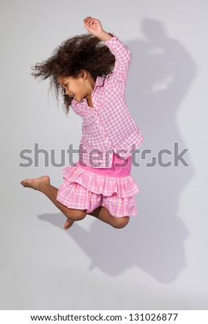 Portrait of cute Young African American girl jumping, over gray background - stock photo