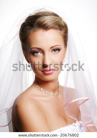 Portrait of cute young bride wearing the white vial. Fashion wedding shot on a white - stock photo