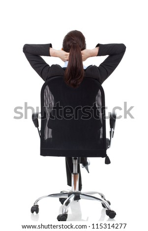 portrait of cute young business woman from behind dreaming, resting on office chair with hands behind her head - stock photo