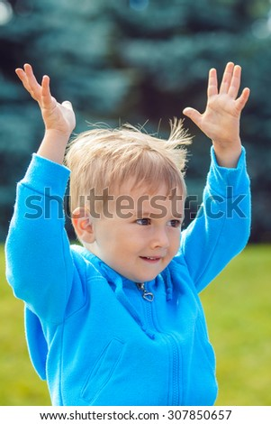 portrait of cute young Caucasian little boy with blond hair, dark brown eyes with funny face expression in blue hoodie outside in park on summer day, backlit with sun from behind, rim light - stock photo