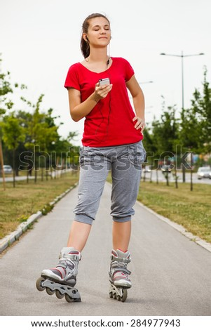 Portrait of cute young girl in roller skates listening music.Sporty girl listening music - stock photo