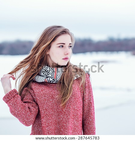 portrait of cute young girl on winter background - stock photo