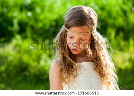 Portrait of cute young girl wearing ribbon headband outdoors. - stock photo