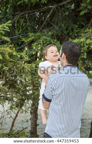 Portrait of dad holding his son by the arm laughing in a park - stock photo