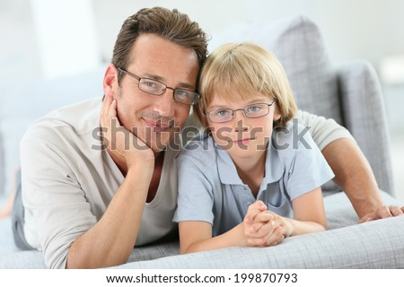 Portrait of daddy and son wearing eyeglasses - stock photo