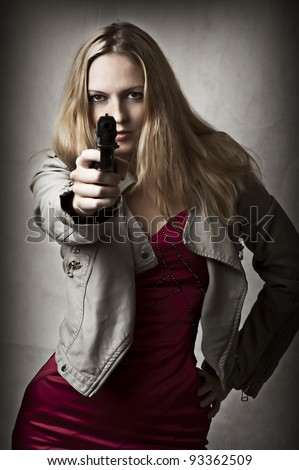 Portrait of dangerous sexy blond woman with hand gun - stock photo
