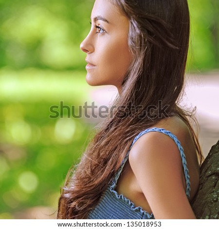 Portrait of dark-haired beautiful young woman in profile, against background of summer green park. - stock photo