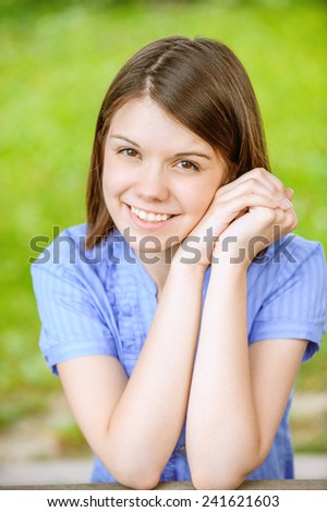 Portrait of dark-haired pretty young woman propping up her face with hands at summer green park - stock photo