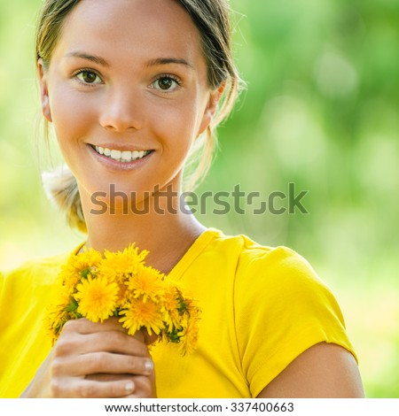 Portrait of dark-haired smiling beautiful young woman in yellow blouse with a bouquet of dandelions, against green of summer park. - stock photo