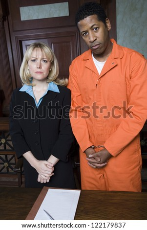 Portrait of dejected advocate standing with fettered prisoner - stock photo