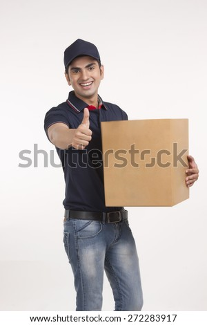 Portrait of delivery man carrying cardboard box while gesturing thumbs up against white background - stock photo